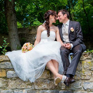 Hochzeit-in-Moeckmuehl-Schloss-Assumstadt-gluckliches-Brautpaar-sitzend-auf-einer-Wand-Fotograf-Natalja-Frei-Videograf-Sergej-Metzger