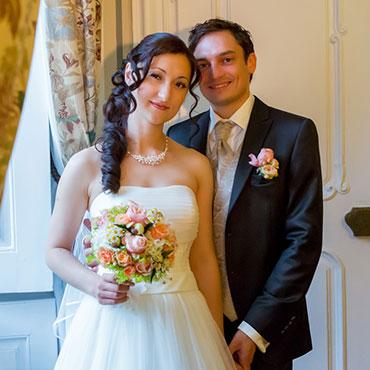 Hochzeit-in-Moeckmuehl-Schloss-Assumstadt-glueckliches-Brautpaar-mit-Brautstrauß-stehend-Hand-in-Hand-am-Fenster-Fotograf-Natalja-Frei-