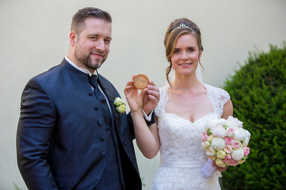 Brautpaar-mit-personalisiertem-Gebäck-Präsentieren-Sergej-Metzger-Hochzeitsvideo-in-Hannover-Fotograf-Hochzeit-Hildesheim