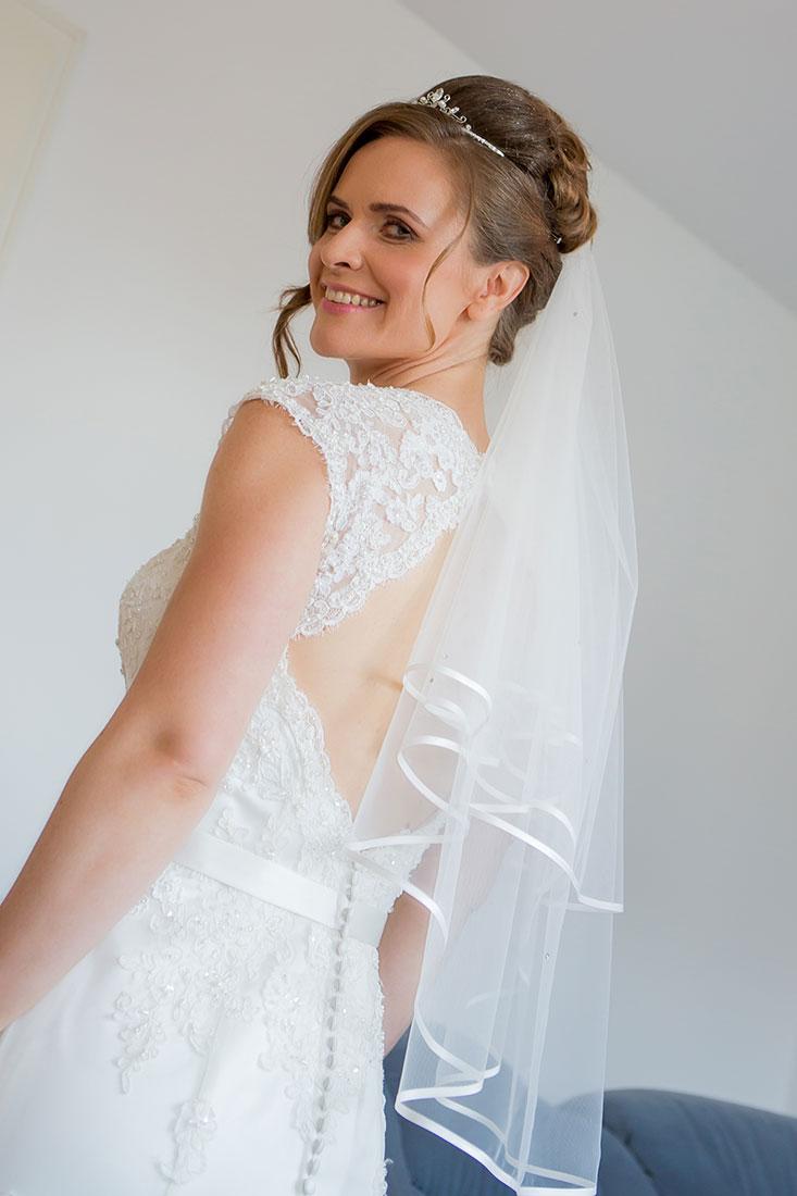 Getting-ready-Braut-mit-Schleier-Rücken-zur-Kamera-Sergej-Metzger-Hochzeitsvideo-in-Hannover-Fotograf-Hochzeit-Hildesheim