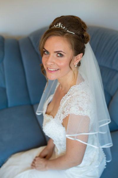 Getting-ready-Brautkleid-Braut-auf-einer-Sofa--Sergej-Metzger-Hochzeitsvideo-in-Hannover-Fotograf-Hochzeit-Hildesheim