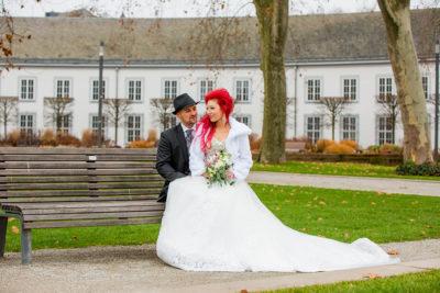 Hochzeit-Schloss-Koblenz-Kaiserin-Augusta-Anlagen-Brautpaar-King-Protea-Braut-rote-Haare-auf-einer-Bank-außergewöhnlich-Sergej-Metzger-Hochzeitsvideo-in-Hannover-Fotograf-Hochzeit-Hildesheim-