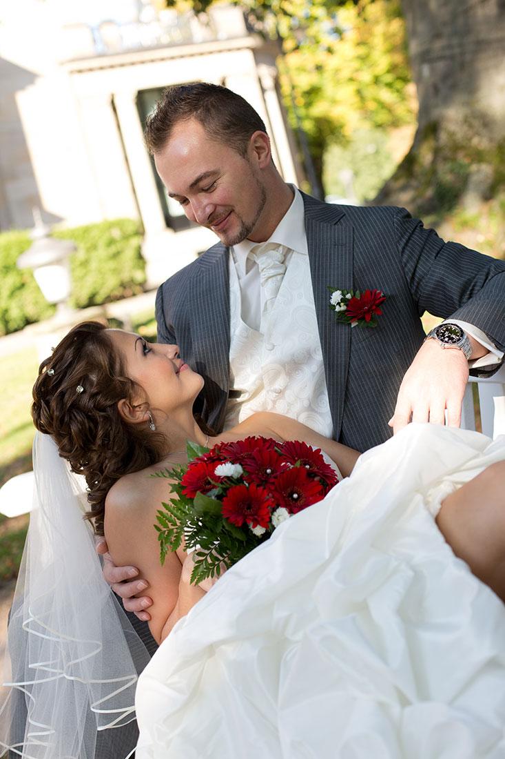 Hochzeit-Kurpark-Wiesbaden-Hochzeitskleid-offene-Beine-liebevoll-Blick-Bank-Sergej-Metzger-Hochzeitsvideo-Hannover-Hildesheim