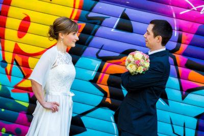 Hochzeit-Limburg-Brautpaar-zu-einander-Graffiti-Wand-farben-Farbenfroh-bunt-Sergej-Metzger-Hochzeitsvideo-Fotograf-Hannover-Hildesheim