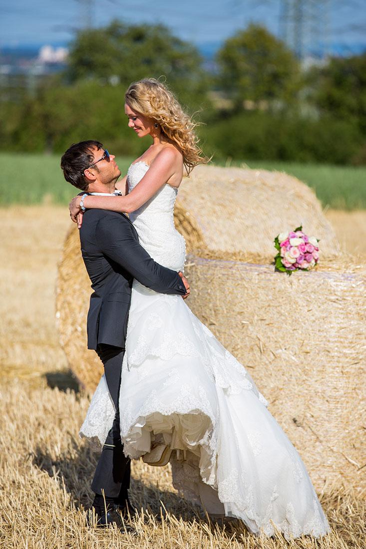 Hochzeit-Mainz-after-wedding-Braut-auf-Händen-Spaß-happy-Glück-Feld-Strohballen--Sergej-Metzger-Hochzeitsvideo-Hildesheim