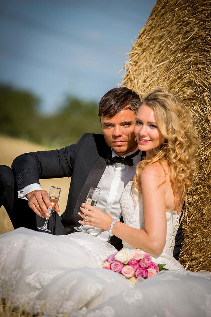 Hochzeit-Mainz-after-wedding-Brautpaar-mit-Sekt-Locken-Sonne-Feld-Strohballen--Sergej-Metzger-Hochzeitsvideo-Hildesheim