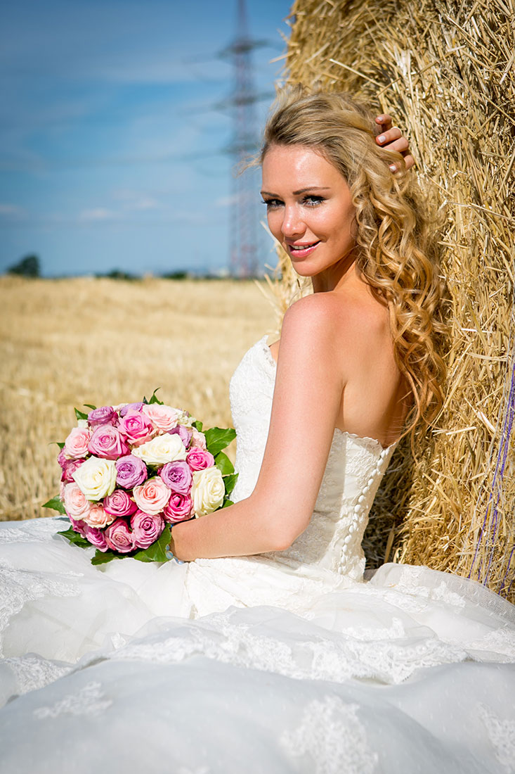 Hochzeit-Mainz-after-wedding-Feld-Braut-sitzt-am-Strohballen--Sergej-Metzger-Hochzeitsvideo-Hildesheim