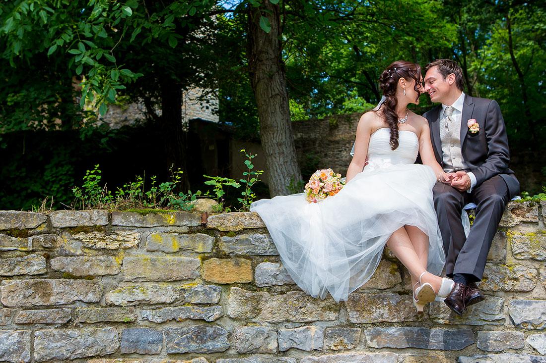 Hochzeit-Schloss-Assumstadt-Möckmühl-Brautpaar-sitzend-Stein-Wand-romantisch-Sergej-Metzger-Hochzeitsvideo-Fotograf-Hannover-Hildesheim