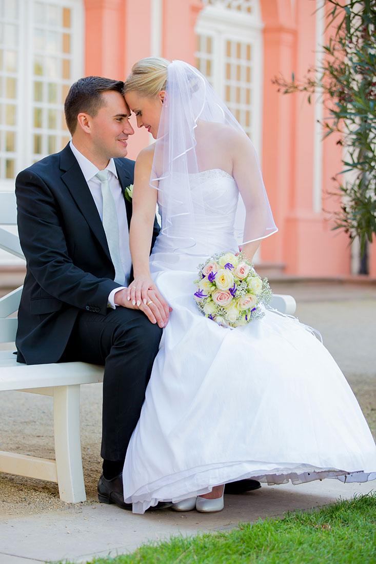 Hochzeit-Wiesbaden-Schloss-Biebrich-Brautpaar-auf-Bank-dem-Schoß-Sergej-Metzger-Hochzeitsvideo-Hannover-Fotograf-Hildesheim