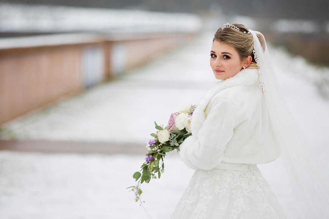 Hochzeit-im-Winter-Osterode-Sössetalsperre--Brautpaar-romantisch-liebevoll-Braut-schaut-in-die-Kamera--Sergej-Metzger-Hochzeitsvideo-in-Hannover-Fotograf
