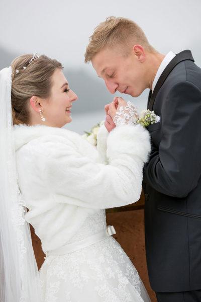 Hochzeit-im-Winter-Osterode-Sössetalsperre--Brautpaar-romantisch-liebevoll-Hände-wärmen-mit-dem-Atem-Braut-lacht--Sergej-Metzger-Hochzeitsvideo-in-Hannover