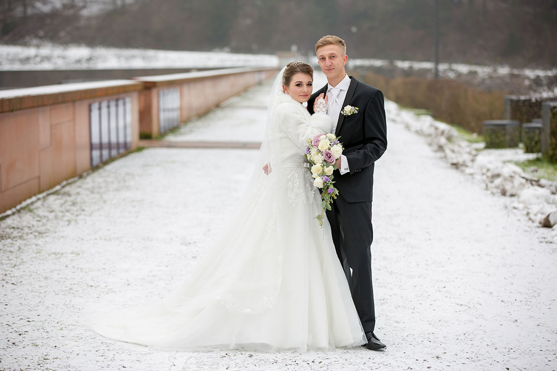 Hochzeit-im-Winter-Osterode-Sössetalsperre--Brautpaar-romantisch-liebevoll-Junge-Familie-Schnee-Brautstrauß--Sergej-Metzger-Hochzeitsvideo-in-Hannover-Fotograf