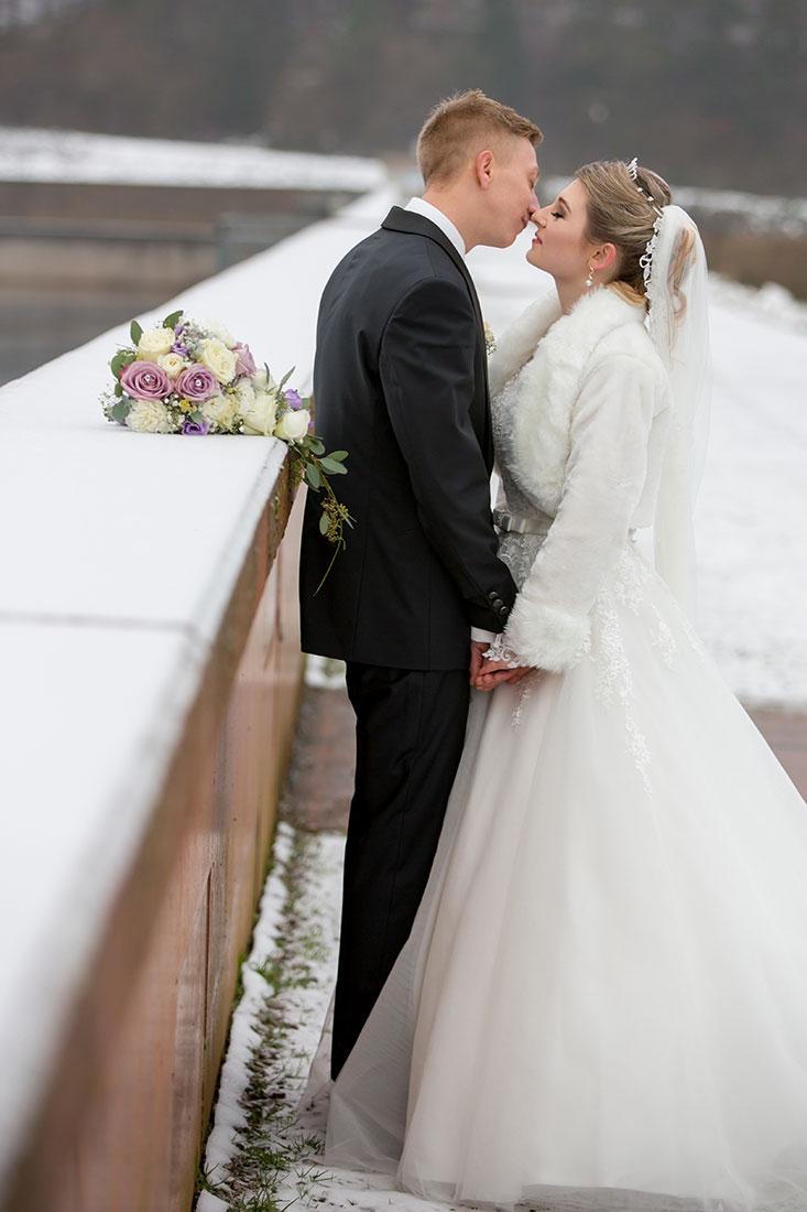 Hochzeit-im-Winter-Osterode-Sössetalsperre--Brautpaar-romantisch-liebevoll-Kuss-Hand-in-Hand--Sergej-Metzger-Hochzeitsvideo-in-Hannover-Fotograf-Hochzeit