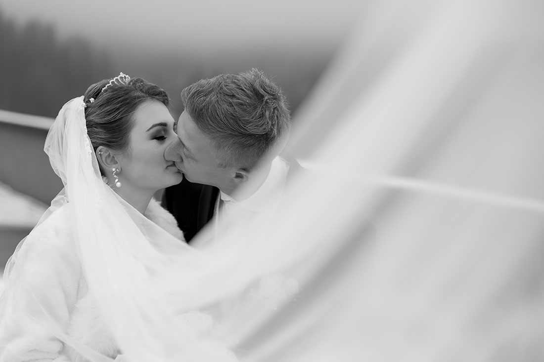 Hochzeit-im-Winter-Osterode-Sössetalsperre--Brautpaar-romantisch-liebevoll-Kuss-schwarz-weiß-langer-Schleier--Sergej-Metzger-Hochzeitsvideo-in-Hannover-Fotograf