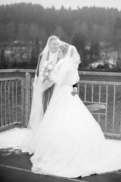 Hochzeit-im-Winter-Osterode-Sössetalsperre--Brautpaar-romantisch-liebevoll--schwarz-weiß-Unter-dem-langen-Schleier--Sergej-Metzger-Hochzeitsvideo-in-Hannover