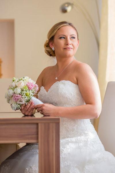 Hochzeit-in-Darmstadt-getting-ready-Braut-am-Fenster-am-Tisch-Brautstrauß-Sergej-Metzger-Hochzeitsvideo-in-Hannover-Fotograf-Hochzeit-Hildesheim