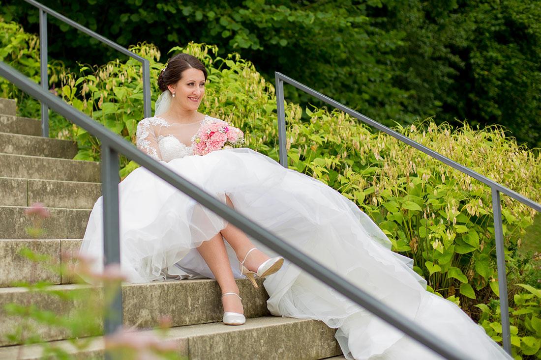 Hochzeit-in-Hemer-Sauerlandpark-Hemer-Brautpaar-Sergej-Metzger-Hochzeitsvideo-in-Hannover-Fotograf-Hildesheim-Braut-auf-Treppen-nackte-Beine-unter-dem-Kleid