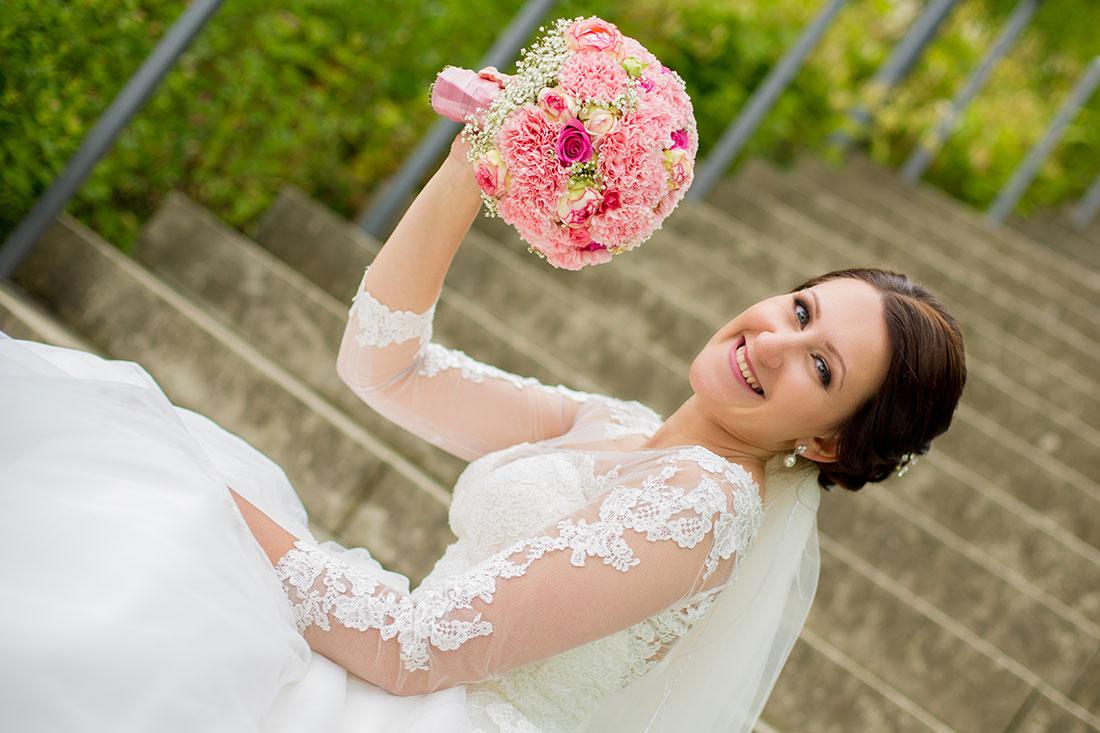 Hochzeit-in-Hemer-Sauerlandpark-Hemer-Brautpaar-Sergej-Metzger-Hochzeitsvideo-in-Hannover-Fotograf-Hildesheim-Freuliche-Braut-mit-Brautstrauß-sitzend-auf-Treppen