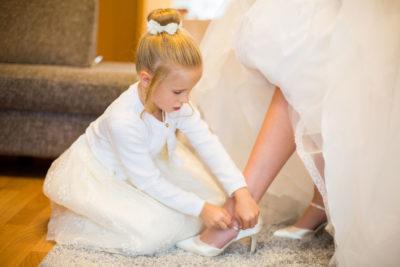 Hochzeit-in-Hemer-Sauerlandpark-Hemer-Brautpaar-Sergej-Metzger-Hochzeitsvideo-in-Hannover-Fotograf-Hildesheim-Mädchen-bindet-Brautschuhe-liebevoll-getting-ready