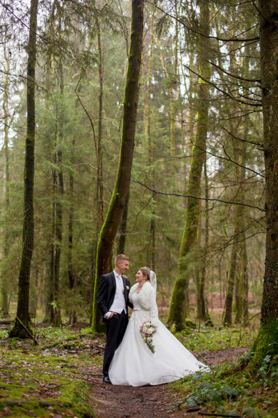Hochzeit-in-Osterode-Hochzeitsbilder-Brautpaar-im-Wald-hohe-Bäume-Waldweg--Sergej-Metzger-Hochzeitsvideo-in-Hannover-Fotograf-Hochzeit-Hildesheim