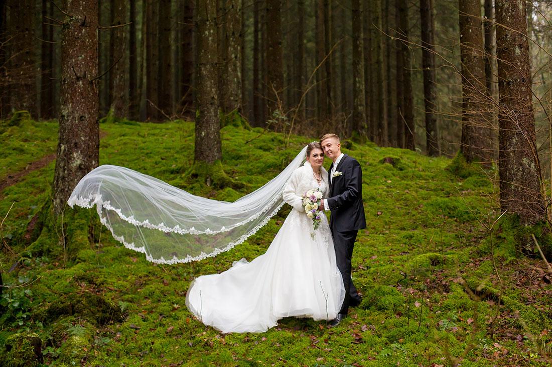 Hochzeit-in-Osterode-Hochzeitsbilder-im-Wald-Brautpaar-langer-schleier-fliegt-in-der-Luft--Sergej-Metzger-Hochzeitsvideo-in-Hannover-Fotograf-Hochzeit-Hildesheim