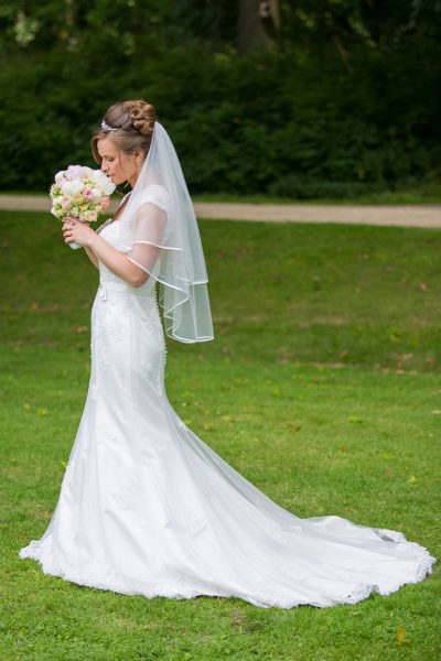 Hochzeit-in-Recklinghausen-Schlosspark-Herten-Braut-auf-der-Wiese-riecht-an-ihrem-Brautstrauß-Sergej-Metzger-Hochzeitsvideo--Hannover