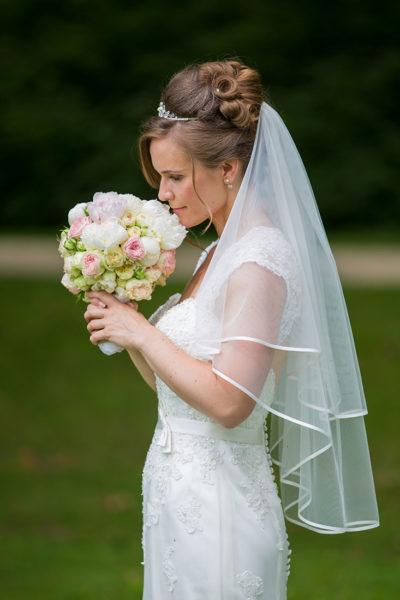 Hochzeit-in-Recklinghausen-Schlosspark-Herten-Braut-auf-der-Wiese-riecht-an-ihrem-Brautstrauß-nahe-Sergej-Metzger-Hochzeitsvideo