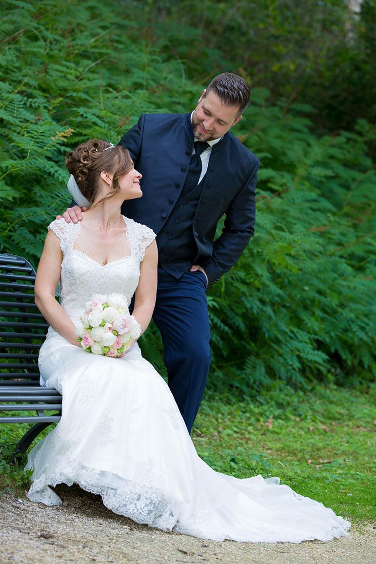 Hochzeit-in-Recklinghausen-Schlosspark-Herten-Brautpaar--auf-einer-Bank-schauen-einander-an-Sergej-Metzger-Hochzeitsvideo-in-Hannover