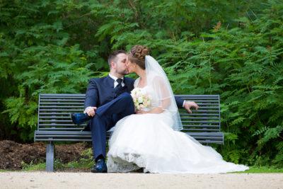 Hochzeit-in-Recklinghausen-Schlosspark-Herten-Brautpaar-küsst-sich-auf-einer-Bank-im-Park-Sergej-Metzger-Hochzeitsvideo-in-Hannover