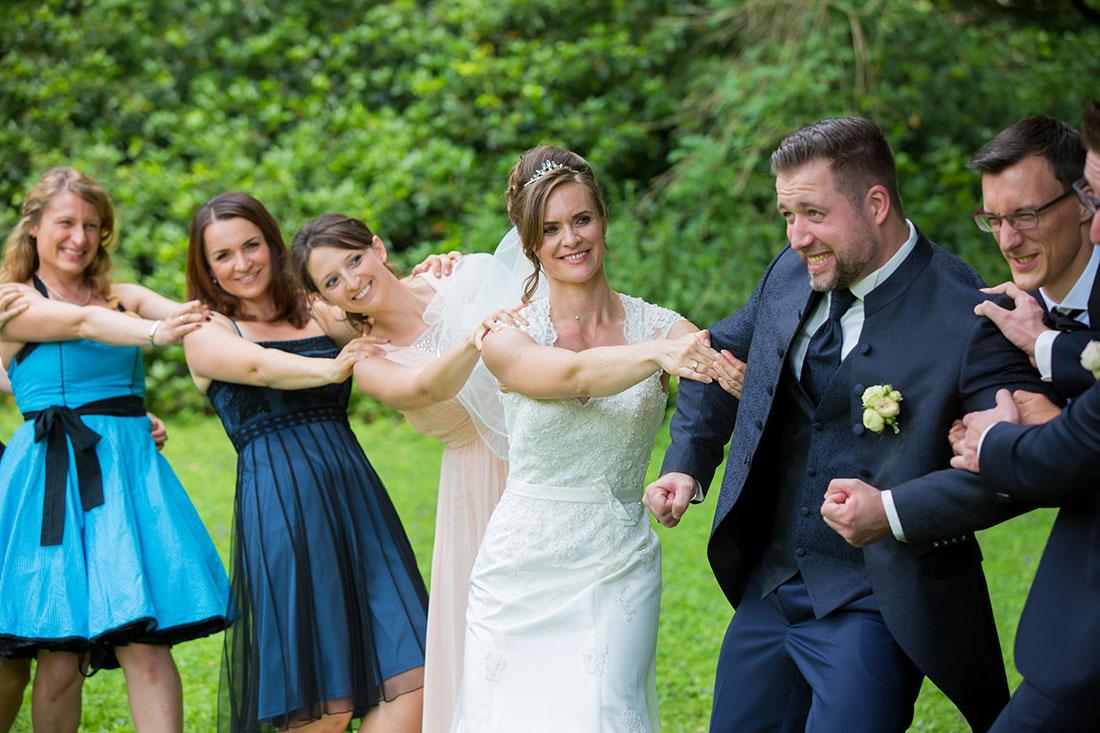 Hochzeit-in-Recklinghausen-Schlosspark-Herten-Gruppenbild-Brautpaar-mit-Freunden-Braut-zieht-Bräutigam-lustiges-Bild-Sergej-Metzger