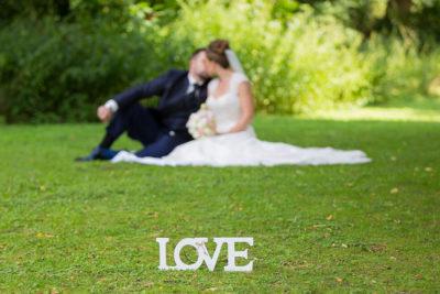 Hochzeit-in-Recklinghausen-Schlosspark-Herten-Love-Dekoration-Brautpaar-küsst-sich-im-Hintergrund-Sergej-Metzger-Hochzeitsvideo