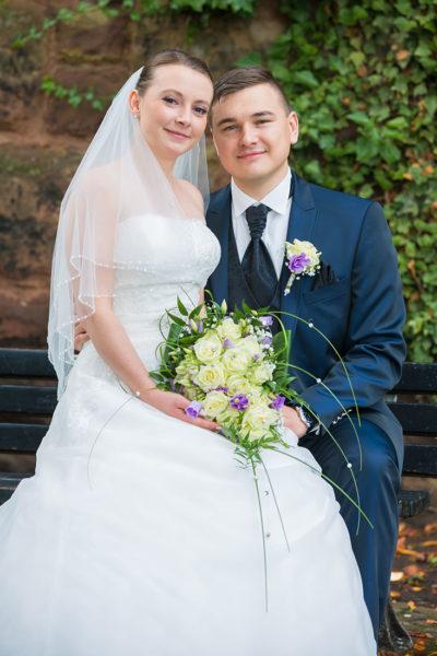 Hochzeit-in-Saarbrücken-Schloss-Schlossgarten-Brautpaar-auf-einer-Bank-auf-Schoß-Sergej-Metzger-Hochzeitsvideo-in-Hannover-Fotograf-Hochzeit-Hildesheim