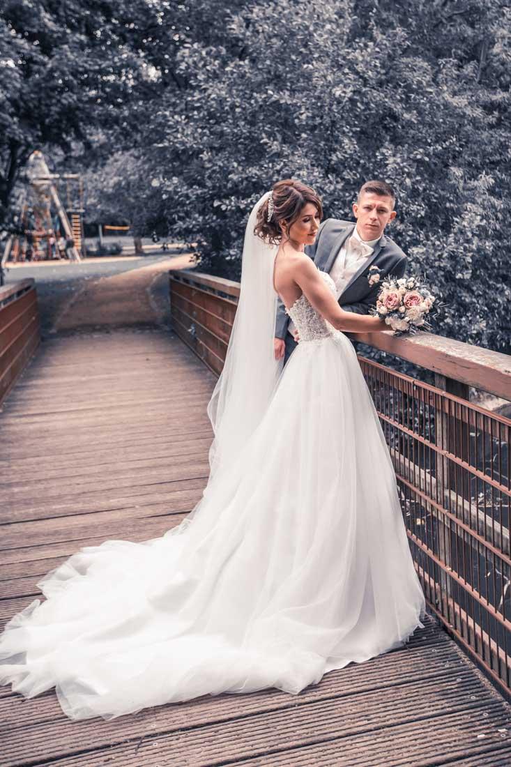 Hochzeit in Herford Aawiesenpark Herford Hochzeitsfotografin Natalja Frei Hochzeitsvideograf Sergej Metzger auf Brücke Schleppe